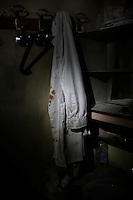 A blood-stained doctor's robe hangs on the walls of the Dar Al-Shifa hospital after it was destroyed by a regime fighter jet on November 21, 2012.