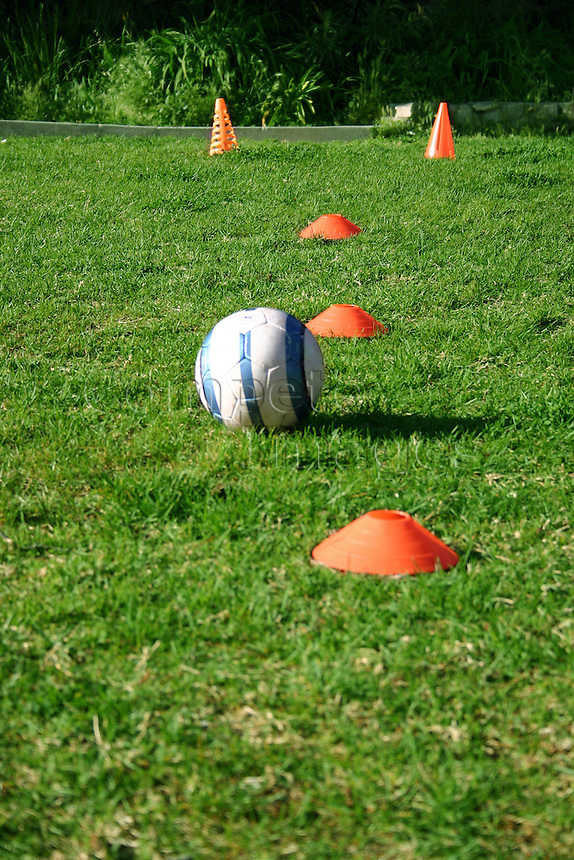 Football placed between practise cones on field