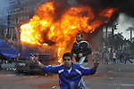protesters stand next to a police vehicle that was set on fire during clashes between protesters and security forces at Tahrir Square in Cairo November 19, 2011. Clashes erupted between riot police and protesters in Cairo's Tahrir square on Saturday after police dispersed a sit-in by demonstrators demanding the ruling military transfer power swiftly to a civilian government. Photo by Ahmed Asad