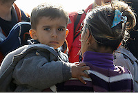 Pictured: A young boy looks puzzled as he is carried by his mother to safety Thursday 27 November 2014<br />