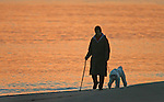 A lady walks her dog on Crissy Field Beach during twilight in the Presido of San Francisco, California.