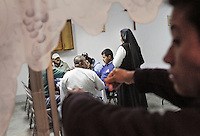 "Mother Ines (at right in background), the Catholic nun who manages the ""Casa Migrante"", an immigrant shelter in Tecate, Baja California, Mexico, talks to a group of immigrants during dinner at her facility on February 7, 2013.  This immigrant shelter houses and feeds thousands of immigrants every year. With a total capacity of 40 beds, male migrants can stay in the premises for a total of 4 nights before moving on. Places such as Casa Migrante are popular amongst immigrants and deportees making their way back into the United States. (Javier Manzano / For The Washington Post)."