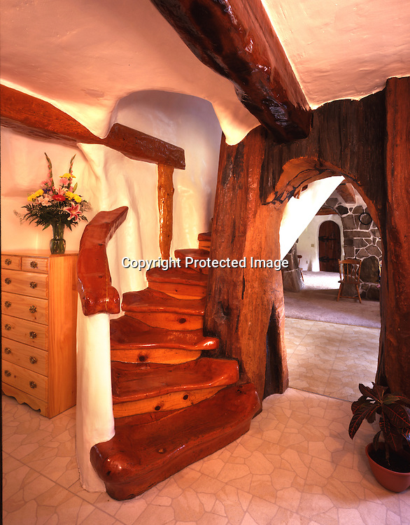 A sensuous stairway meanders its way to the second story children's bedroom in this Storybook style home.