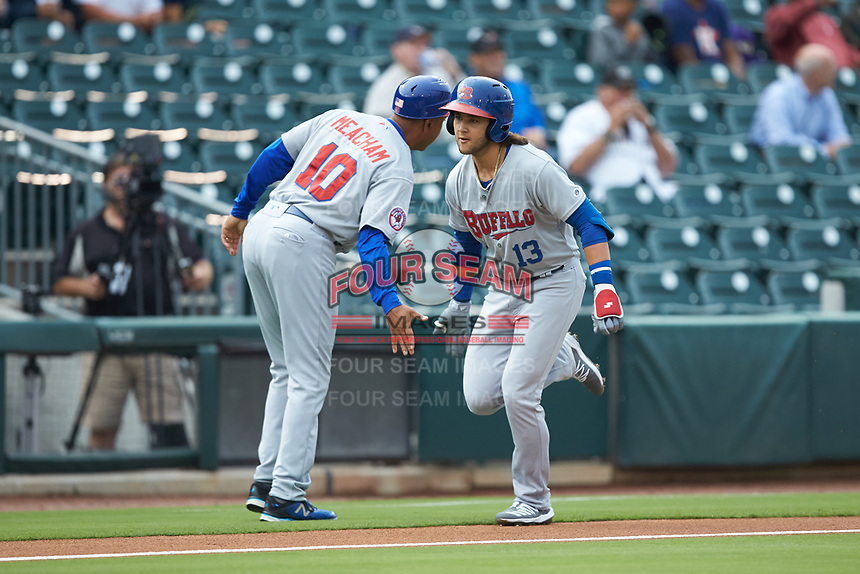 Buffalo Bisons manager Bobby Meacham (10) slaps hands with Bo Bichette (13) as he rounds third base after hitting a home run against the Caballeros de Charlotte at BB&T BallPark on July 23, 2019 in Charlotte, North Carolina. The Bisons defeated the Caballeros 8-1. (Brian Westerholt/Four Seam Images)