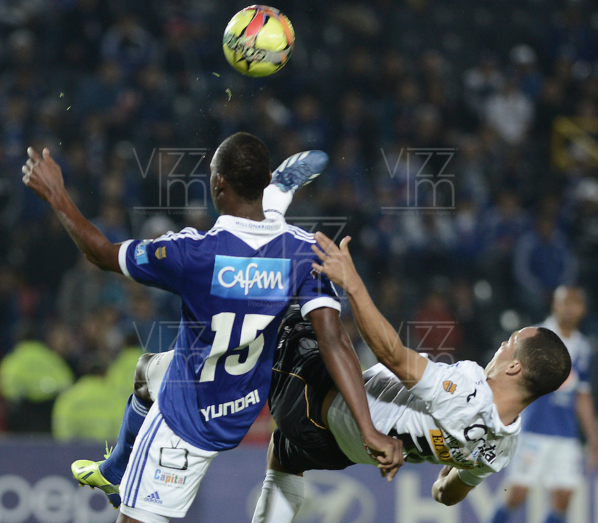BOGOTÁ -COLOMBIA, 07-12-2013. Erick Moreno (Izq.) jugador de Millonarios disputa el balón con Sebastian Puerta (Der.) jugador de Once Caldas durante partido por la fecha 6 de los cuadrangulares finales de la Liga Postobón  II 2013 jugado en el estadio Nemesio Camacho el Campín de la ciudad de Bogotá./ Erick Moreno (L) player of Millonarios fights for the ball with Sebastian Puerta (R) player of Once Caldas during match for the 6th date of final quadrangulars of the Postobon  League II 2013 played at Nemesio Camacho El Campin stadium in Bogotá city. Photo: VizzorImage/Gabriel Aponte/STR