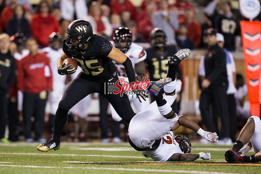 Cam Serigne (85) of the Wake Forest Demon Deacons avoids the tackle attempt by Chucky Williams (22) of the Louisville Cardinals during second half action at BB&T Field on October 30, 2015 in Winston-Salem, North Carolina.  The Cardinals defeated the Demon Deacons 20-19.  (Brian Westerholt/Sports On Film)