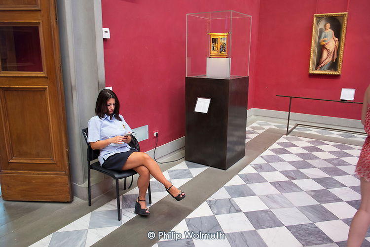 Attendant using a smartphone in the Uffizi gallery, Florence, Italy.
