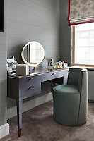 In a bedroom alcove, a marble topped dressing table with a circular mirror