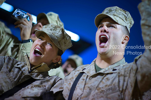Al Asad Air Base, Iraq - December 19, 2008 -- United States Marine Corporal Chantel Saville (left) and Sergeant Jonathan Oaks cheer at the introduction of  Grammy award winning musician Kid Rock and Zach Brown during the 2008 USO Holiday Tour stop at Al Asad Sir Base, Iraq, Friday, December 19, 2008.  Tour host United States Navy Admiral Mike Mullen, chairman of the Joint Chiefs of Staff, along with his wife Deborah, welcomed comedians John Bowman, Kathleen Madigan and Lewis Black; actress Tichina Arnold; American Idol contestant and country musician Kellie Pickler and Grammy award winning musician Kid Rock on the tour bringing music and entertainment to service members and their families stationed overseas. .Credit: Chad J. McNeeley - DoD via CNP