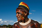 Xingu Indigenous Park, Mato Grosso State, Brazil. Aldeia Kuikuro - central village. Festival of Taquara; Cacique wearing a feather cocaa and ear plugs.