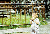 A young boy eating an apple in rural China