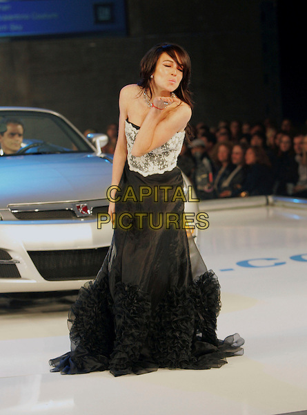 LINDSAY LOHAN.The 5th Annual GM Ten Fashion Show held on Vine St. in Hollywood, California, USA..February 28th, 2006.Ref: DVS.catwalk full length black white lace strapless sheer ruffles blowing kiss gesture.www.capitalpictures.com.sales@capitalpictures.com.Supplied By Capital PIctures