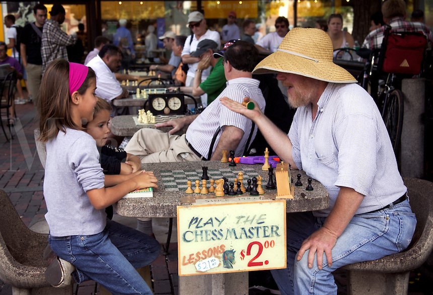 Chess master teaching young children about the game of chess at outdoor table on plaza at Harvard Square across from Harvard University, Cambridge, M