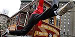 A man hangs off a cable car in San Francisco, California.