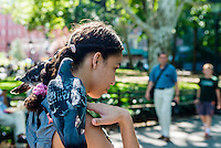 New York, NY - 31 July 2015 - Woman walking through Washington Square Park with a pigeon on each shoulder. On July 22nd 200 to 300 of the parks pigeons went missing.