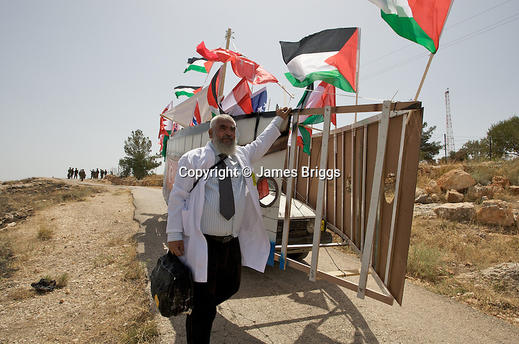 A Palestinian Doctor is allowed by IDF soldiers to recover a recreation of the Mavi Marmara built by the villagers of Bil'in to honour those killed during the Israeli raid on the Turkish aid ship during the villager's weekly protest against the controversial West Bank barrier, near Ramallah on 04/06/2010.