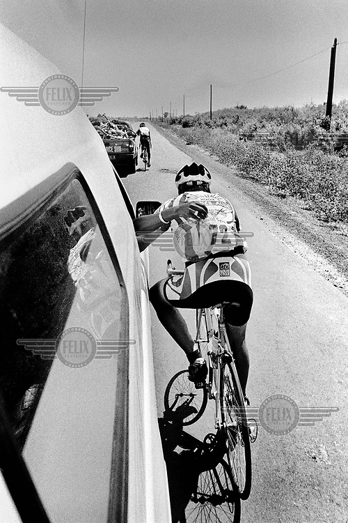 The third stage of the Tour du Senegal, when average temperatures reached 42 degrees Celsius. A few cyclists, including these two Frenchmen, fell away from the pack and had to be helped by backup vehicles..The Tour du Senegal, a two-week cycle race, traverses the country with a total distance of 1168km.