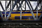 ZALTBOMMEL - Een intercity trein, een dubbeldekker, van de Nederlandse Spoorwegen rijdt schijnbaar klem tussen de stalen spanten van de spoorbrug met hoge snelheid over de rivier Waal op het traject Utrecht - Den Bosch. COPYRIGHT TON BORSBOOM