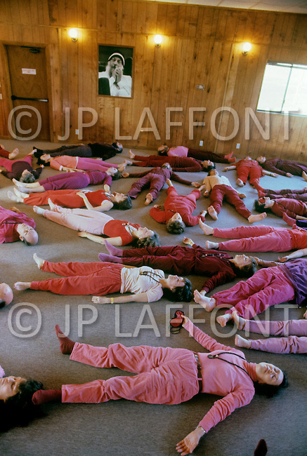 Wasco, Oregon, February 1984:  Disciples of Bhagwan Rajneesh in a group mediation session. Rajneeshpuram, was an intentional community in Wasco County, Oregon, briefly incorporated as a city in the 1980s, which was populated with followers of the spiritual teacher Osho, then known as Bhagwan Shree Rajneesh. The community was developed by turning a ranch from an empty rural property into a city complete with typical urban infrastructure, with population of about 7000 followers.