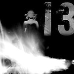 a woman in an evening dress stands behind a wall of flames and in front of the number 13