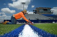 NWA Democrat-Gazette/BEN GOFF @NWABENGOFF<br /> Alejandro Perez trims the rough ends of artificial turf Thursday, July 6, 2017, as a crew from Symmetry Turf out of Mount Pleasant, Texas, replaces the playing surface at Rogers High's Whitey Smith Stadium. The existing turf was ten years old and at the end of its useful lifespan, according to Dan Caley, Rogers Public Schools director of facilities. The indoor practice field at Rogers Heritage has also received new turf as part of the project.