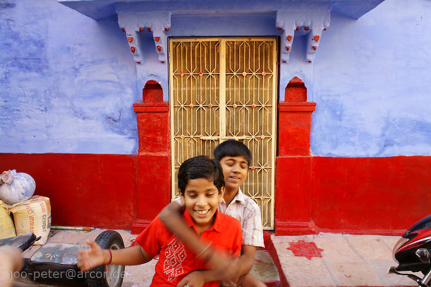 street scene in Jodhpur with kids and blue-red wall painting, Rajastan, India
