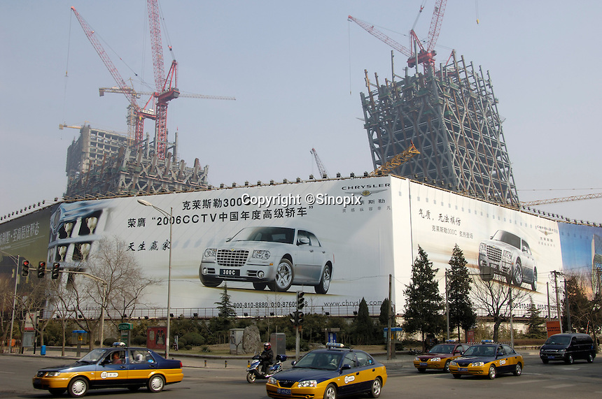 A billboard adverts Chrysler car in Beijing, China. Behind is the new headquarters for China Central Television (CCTV) under construction in Beijing, China.  .