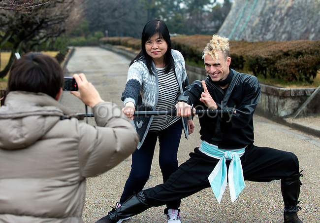 """Ninja Chris  """"Sora"""" O'Neil has his photo taken with a visitor from Hong Kong in the grounds of Nagoya Castle, Aichi Prefecture Japan on Feb. 23, 2017. O'Neil is one of the eight ninja corps who roam the avenues of the castle and Nagoya Airport, jumping from behind trees and bushes to surprise visitors. ROB GILHOOLY PHOTO"""