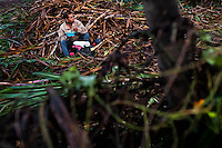 A sugar cane cutter eats breakfast before a shift in a field near Florida, Valle del Cauca, Colombia, 27 May 2012. The Cauca River valley is the booming centre of agriculture and sugar cane cultivation in Colombia. Although the main part of the crop is still refined into a sugar, the global demand of biofuel and ethanol has intensified the sugar cane production in the last years. 85 percent of Colombia's cane crop is still harvested the manual way, employing approximately 30,000 workers. Working six days a week, under harsch labor conditions, the sugar cane cutters earn $4 for every ton of cane they cut, with no access to social benefits due to the tricky system of intermediary contractors and cooperatives.