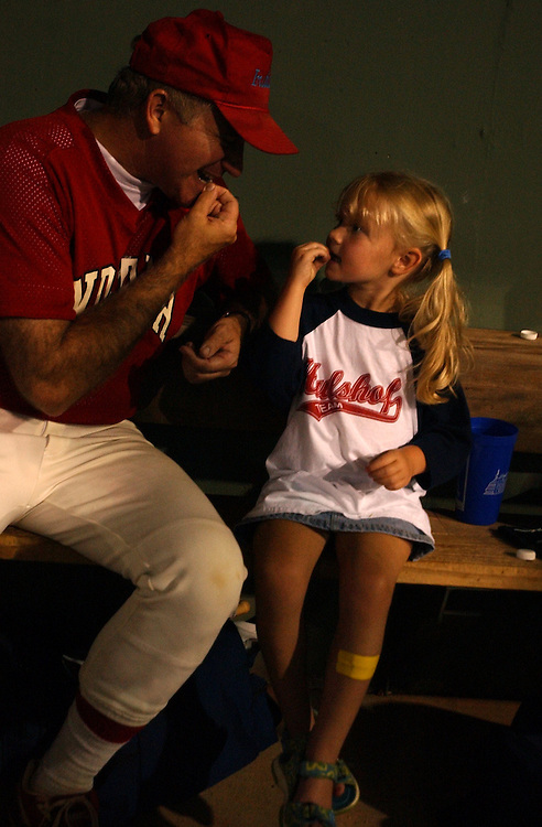 Rep. Steve Buyer, R-Ind., teaches Casey Hulshof, 4, daughter of Rep. Kenny Hulshof, R-Mo., how to eat sunflower seeds at the 2004 Congressional Baseball Game.