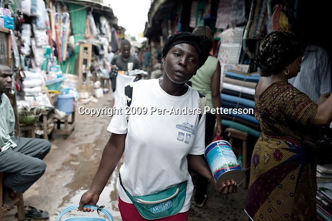BAMENDA, CAMEROON - AUGUST 8: Felicity, age 20, walks in the central market selling the Oldenberger milk powder on August 8, 2009 in Bamenda, Cameroon. It is new on the market and not to easy to convince customers to buy it, as it is more expensive than some other brands on the market. Many small farmers in the area are struggling to cope with low milk prices, expensive inputs and competing with low priced milk powder, that is heavily subsidized by European governments and dumped on international markets such as in Africa. The German company Oldenburger has just started selling powder milk and long life milk on the country. (Photo by Per-Anders Pettersson).....