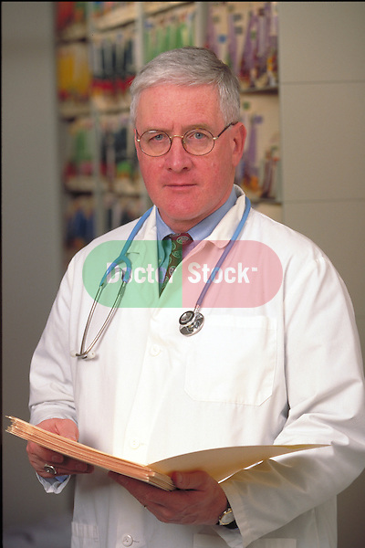 portrait of serious doctor holding medical charts