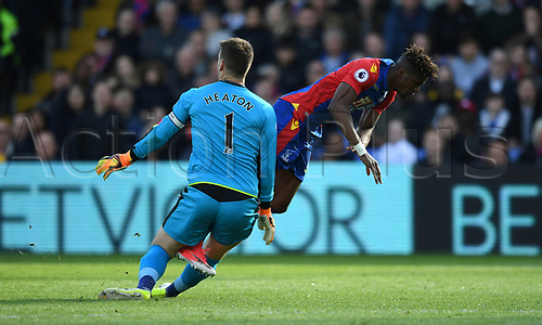 April 29th 2017, Selhurst Park, London England; EPL Premier league football, Crystal Palace versus Burnley; Tom Heaton, Goalkeeper for Burnleyclears away the ball outside his area taking out Wilfried Zaha, Midfielder for Crystal Palace