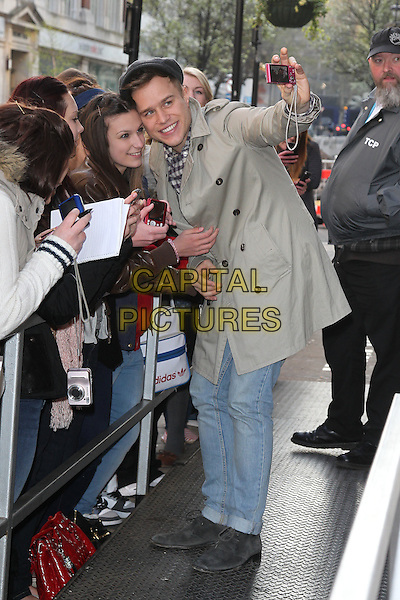 Olly Murs at the studios of BBC Radio 1, London, England..April 2nd, 2012.full length grey gray flat cap hat mac beige trench coat jacket fans camera bending leaning taking picture photograph.CAP/HIL.©John Hillcoat/Capital Pictures .