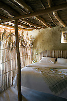 The ceiling, screen and headboard in this bedroom have all been constructed from locally-sourced palmwood