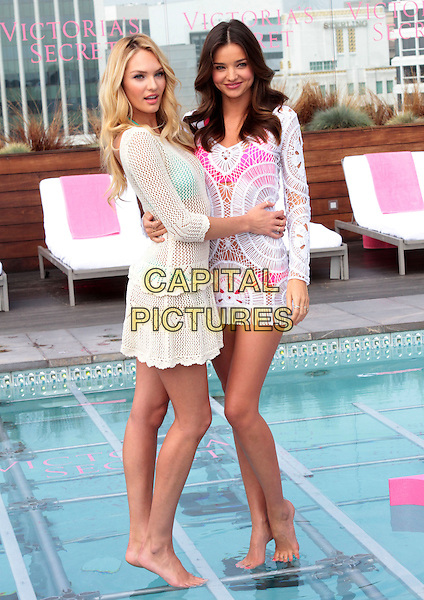 Candice Swanepoel, Miranda Kerr.Victoria's Secret Celebrates its 2012 Swim Collection held at the Thompson Hotel in Beverly Hills, Beverly Hills, California, 29th March 2012..full length models  white crochet dress walking on water standing in swimming pool pink bikini rooftop roof underwater runway arm around .CAP/ADM/SLP/JO.©James Orken/Starlitepics/AdMedia/Capital Pictures.