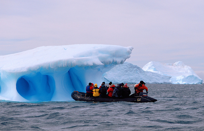 Zodiac approaches an iceberg with a dramatic blue heart. Antarctic Peninsula.