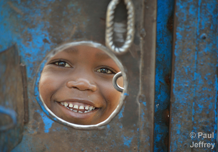 A peers through a hole in the gate around a church compound in the middle of a camp for more than 5,000 displaced people in Riimenze, in South Sudan's Gbudwe State, what was formerly Western Equatoria. Families here were displaced at the beginning of 2017, as fighting between government soldiers and rebels escalated.<br />
