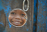 A peers through a hole in the gate around a church compound in the middle of a camp for more than 5,000 displaced people in Riimenze, in South Sudan's Gbudwe State, what was formerly Western Equatoria. Families here were displaced at the beginning of 2017, as fighting between government soldiers and rebels escalated.<br /> <br /> Two Catholic groups, Caritas Austria and Solidarity with South Sudan, have played key roles in assuring that the displaced families here have food, shelter and water.<br /> The camp formed around the Catholic Church in Riimenze as people fled violence in nearby villages for what they perceived as the safety offered by the church.