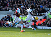 Pictured: Wilfried Bony of Swansea (R) closely followed by James Tomkins (L) of West Ham. 01 February 2014<br />