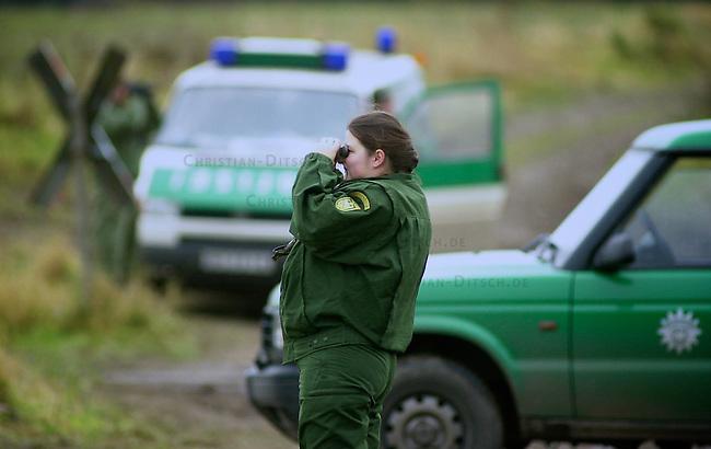 Polizei sichert Castor-Transport im November 2002<br /> Ein Transport von zwoelf Castoren aus der franzoesichen Wiederaufbereitungsanlage La Hague traf am Mittwoch den 13. November 2002 im Wendland ein. Trotz Blokaden auf den Schienen, gelang es den Zug mit nur wenigen Stunden Verspaetung an sein Ziel zu bringen. Immer wieder hatten sich Umweltschuetzer auf den Gleisen festgekettet um den Transport zu verhindern, wurden jedoch von der Polizei geraeumt.<br /> Im Bild: Eine Beamte des Bundesgrenzschutz (BGS - Bundespolizei) sichert an einem Bahnhuebergang bei Rohsdorf die Transportstrecke.<br /> Fuer das erste Novemberwochenende 2010 ist wieder ein Transport von 13 stark radioaktiven Castorbehaeltern nach Gorleben geplant. Die Antiatom-Bewegung plant fuer diesen Transport umfangreiche Proteste und kuendigte an, an den Gleisen den Schotter zu entfernen.<br /> 13.11.2002, Rohsdorf<br /> Copyright: Christian-Ditsch.de<br /> [Inhaltsveraendernde Manipulation des Fotos nur nach ausdruecklicher Genehmigung des Fotografen. Vereinbarungen ueber Abtretung von Persoenlichkeitsrechten/Model Release der abgebildeten Person/Personen liegen nicht vor. NO MODEL RELEASE! Nur fuer Redaktionelle Zwecke. Don't publish without copyright Christian-Ditsch.de, Veroeffentlichung nur mit Fotografennennung, sowie gegen Honorar, MwSt. und Beleg. Konto: I N G - D i B a, IBAN DE58500105175400192269, BIC INGDDEFFXXX, Kontakt: post@christian-ditsch.de<br /> Bei der Bearbeitung der Dateiinformationen darf die Urheberkennzeichnung in den EXIF- und  IPTC-Daten nicht entfernt werden, diese sind in digitalen Medien nach &sect;95c UrhG rechtlich geschuetzt. Der Urhebervermerk wird gemaess &sect;13 UrhG verlangt.]