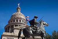 USA and Texas Flags fly next to the Texas Ranger statue at the Texas State Capitol in downtown Austin, Texas.