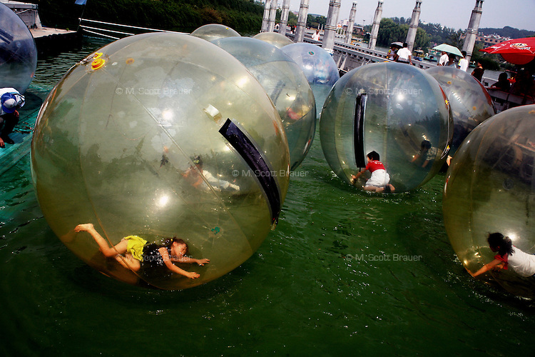 Children play in giant inflatable balls on a lake in the White Horse Sculpture Park in Nanjing, China.