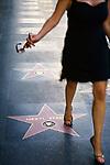 A woman walks along Hollywood Blvd.'s Walk of Fame