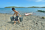 Ray Elmadorial, 15, carries fresh water ashore on Manipulon, a small island off the coast from the town of Estancia, in the Philippines province of Iloilo. Families living here have to fetch their fresh water from the nearby island of Bayas, seen in the background. The islands were hit hard by Typhoon Haiyan in November 2013. The storm was known locally as Yolanda.  Most of the island's boats were damaged or destroyed. Residents of this island have received assistance from the ACT Alliance.