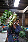 INDONESIA, Flores, Reung, carrying leafy greens for sale at the Reung Market