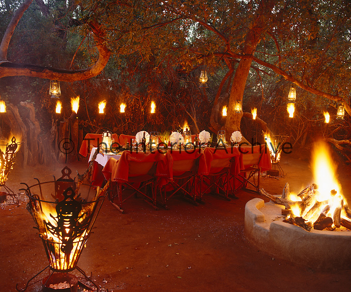 Flares and storm lanterns light this outdoor dining area while braziers and an open fire keep off the chill of the approaching night