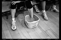 Player Li Yilin of Tsinghua University Affiliated Middle School basketball team submerges his foot into a bucket of ice after an ankle injury sustained during a training session at Tsinghua University Affiliated Middle School in Beijing, January 2012.