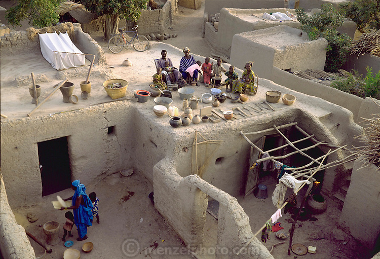 The Natomo family with all of their possessions on the roof of their home in Kouakourou, Mali. Published in Material World, page 14. The Natomo family lives in two mud brick houses in the village of Kouakourou, Mali, on the banks of the Niger River. They are grain traders and own a mango orchard. According to tradition Soumana is allowed to take up to four wives; he has two. Wives Pama and Fatoumata are partners in the family and care for their many children together.