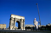 Woman wearing traditional dress, walking along the footpath with Porte d'Aix triumphal arch in the background, Marseille, France.